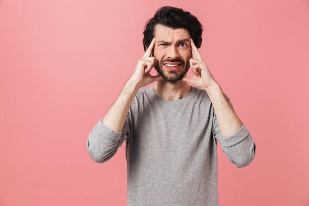 Bello stanco giovane barbuto uomo bruna che indossa un maglione in piedi sopra il bianco, sofferente di un mal di testa