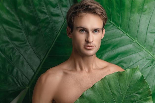 Bel uomo in topless con una foglia verde tra le mani e in posa su uno sfondo di piante