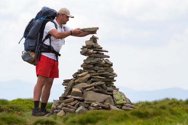 Uomo turistico bello con lo zaino che fa il mucchio della piramide delle pietre accese dalla valle erbosa verde della montagna del sole di estate sul cielo blu-chiaro dello spazio della copia