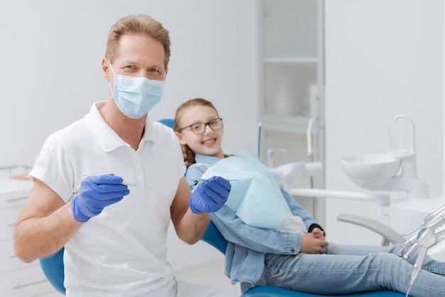 Medico completo addestrato bello che tiene una serie di apparecchiature odontoiatriche per il controllo dei denti dei pazienti mentre lei è seduta su una sedia comoda dietro di lui