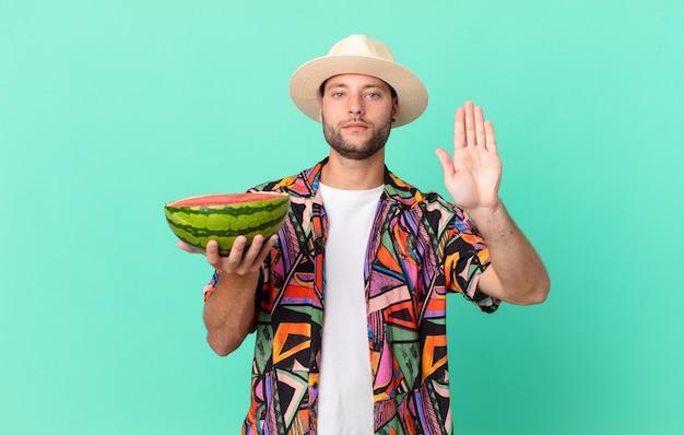 Un bell'uomo viaggiatore dall'aspetto serio che mostra il palmo aperto che fa un gesto di arresto e tiene in mano un'anguria. concetto di vacanze
