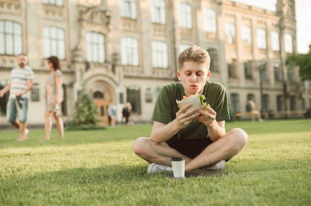 Studente universitario bello che mangia panino appetitoso
