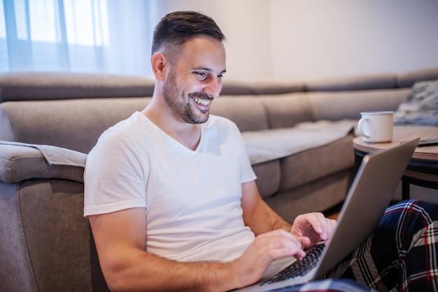 Uomo caucasico non rasato bello in pigiami che si siedono sul pavimento in salone con il computer portatile nel rivestimento e nella battitura a macchina.