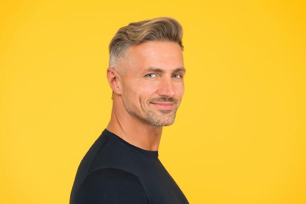 Bell'uomo con la barba lunga. sfondo giallo uomo macho maturo. moda acconciatura maschile. cura della pelle del viso. moda capelli per uomo. concetto di barbiere. ragazzo fiducioso e sorridente. ritratto di carisma.