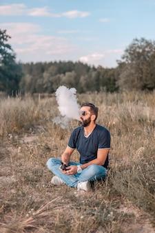 Bello vaper che fuma un dispositivo elettronico per il fumo in una radura della foresta