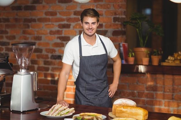 Bel cameriere si chinò su un tavolo da cibo