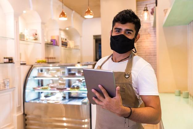 Cameriere bello in maglietta bianca che lavora con la tavoletta in piedi all'interno di una caffetteria indossa una maschera