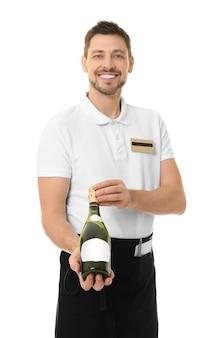Bello cameriere con una bottiglia di vino su sfondo bianco