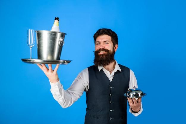Cameriere bello con vassoio da portata e cameriere del refrigeratore per vino nel ristorante con coperchio a cloche in metallo