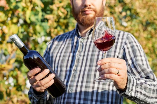 Bel vinificatore tenendo in mano una bottiglia e un bicchiere di vino rosso e assaggiandolo