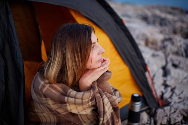 Donna bella che si siede con la mano sotto il mento, sulla spiaggia di pietra, guardando il tramonto.