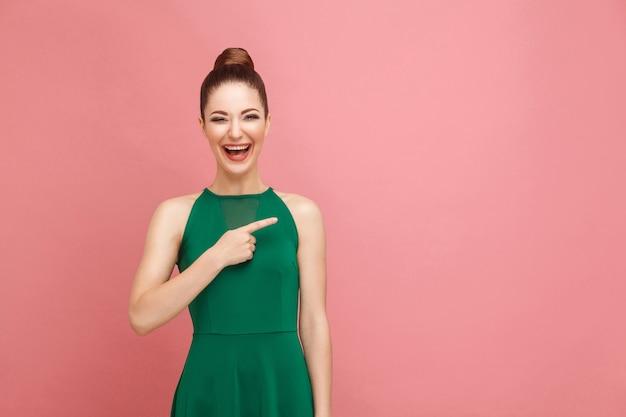 Bella donna a trentadue denti sorridente e puntando il dito sullo spazio della copia. concetto di emozione e sentimenti di espressione. studio girato, isolato su sfondo rosa