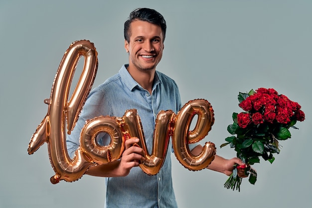 Bel giovane uomo in camicia blu è in piedi con rose rosse e mongolfiera etichettato amore in mano su grigio.