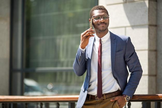 Bel giovane adulto africano uomo in tuta e occhiali, parlando al telefono