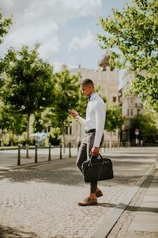 Bel giovane uomo d'affari afroamericano che usa un telefono cellulare su una strada