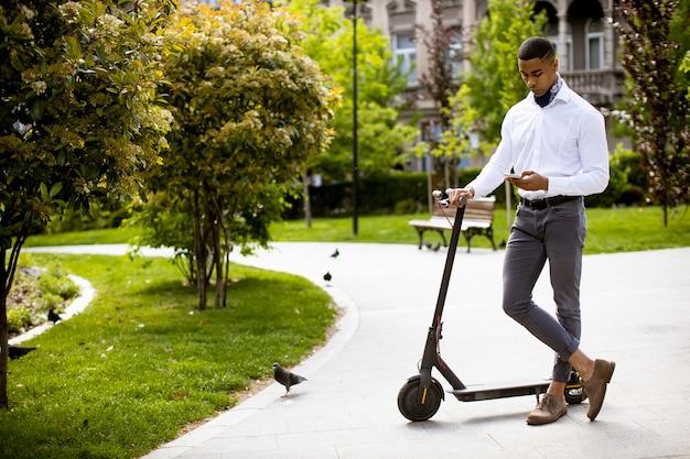 Bel giovane afroamericano utilizzando il telefono cellulare in piedi da scooter elettrico in strada