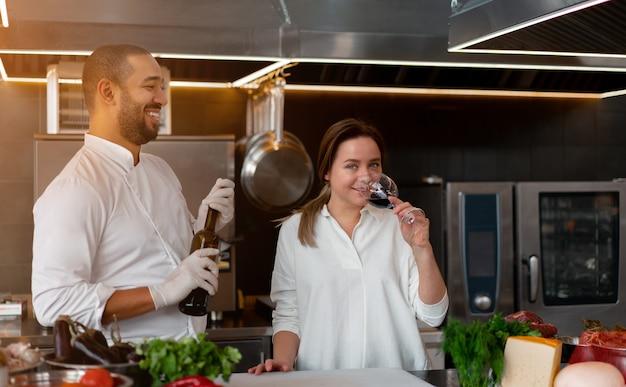Il giovane chef africano bello sta cucinando insieme alla ragazza caucasica in cucina usando l'ingrediente del vino rosso. un cuoco insegna a una ragazza a cucinare. uomo e donna che cucinano nella cucina professionale.