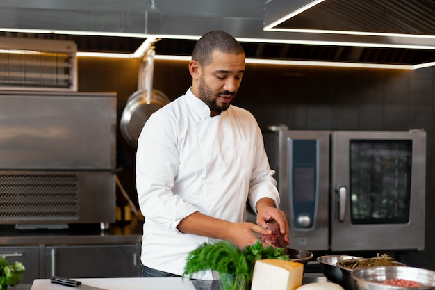 Giovane cuoco unico africano bello che sta nella cucina professionale in ristorante che prepara un pasto delle verdure della carne e del formaggio. ritratto di uomo in uniforme cuoco. concetto di mangiare sano.