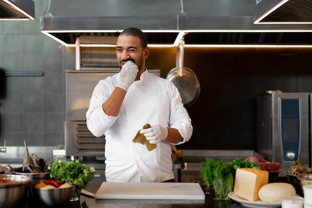 Giovane cuoco unico africano bello che sta nella cucina professionale in ristorante che prepara un pasto delle verdure della carne e del formaggio. ritratto di uomo in uniforme cuoco. assaggia il peperoncino