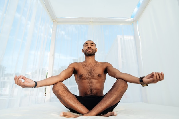 Bel giovane africano in pantaloncini seduto e meditando sul letto della spiaggia