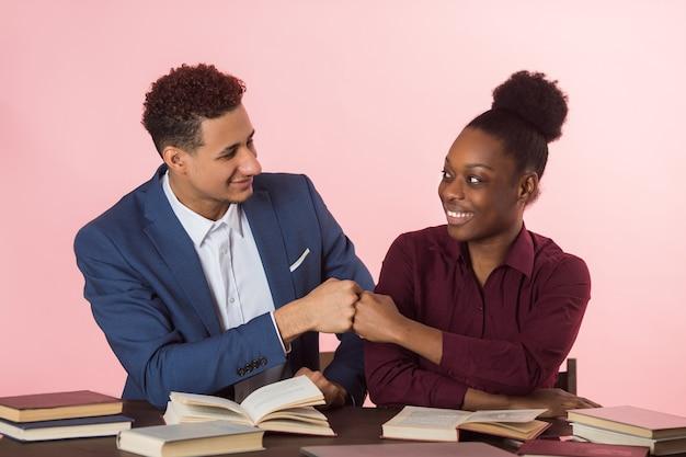 Bel giovane africano uomo e donna che leggono libri al tavolo