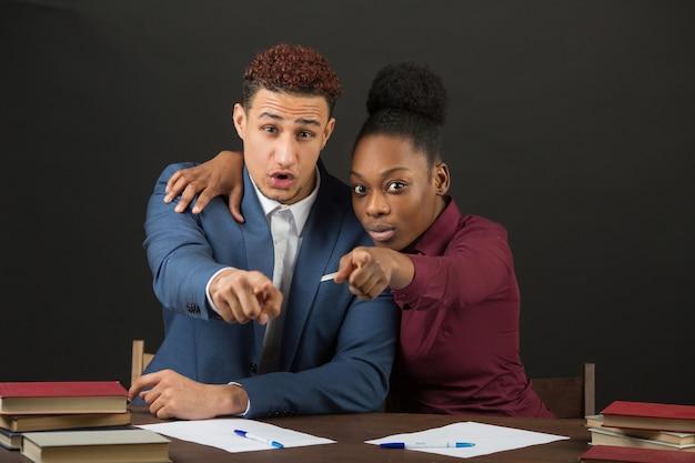 Bel giovane africano e donna al tavolo in classe