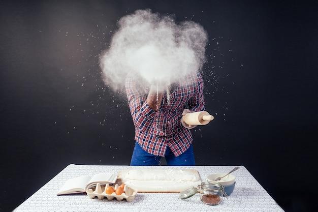 Bello e giovane uomo afro africano che prepara torte fatte in casa american pie da pasta fresca mani sporche di farina, sul tavolo ci sono uova, mattarello e ricettario su uno sfondo nero in studio