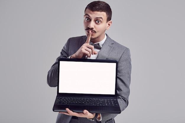 Il giovane uomo d'affari arabo bello con i baffi in vestito grigio tiene il computer portatile