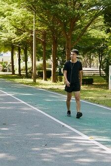 Bel giovane uomo asiatico ragazzo sportivo camminare ascoltando musica di formazione