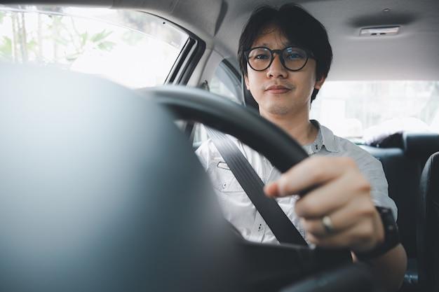 Bel giovane uomo asiatico che usa la cintura di sicurezza mentre guida un'auto