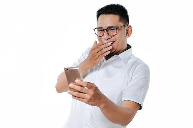 Bel giovane uomo asiatico che indossa occhiali guardando video divertenti sul telefono cellulare, isolato su sfondo bianco