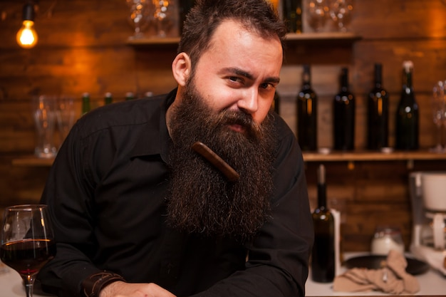 Bel giovane barista che gioca con la barba. grande personalità .