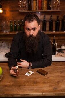 Bel giovane barista che gioca con il suo accendino su misura. sentirsi bene.