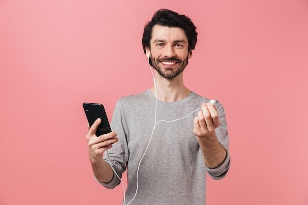 Bel giovane barbuto bruna uomo che indossa un maglione in piedi sopra il rosa, ascoltando musica con gli auricolari, tenendo il telefono cellulare