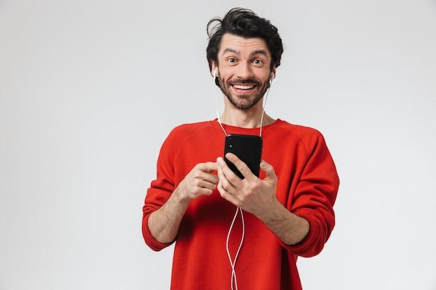Bel giovane barbuto uomo bruna che indossa un maglione in piedi sopra bianco, ascoltando musica con gli auricolari, tenendo il telefono cellulare
