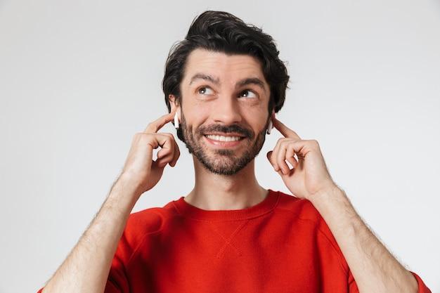 Bel giovane barbuto bruna uomo che indossa un maglione in piedi sopra il bianco, ascoltando musica con gli auricolari