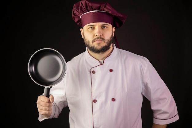 Bel giovane chef barbuto in uniforme tiene una piccola padella