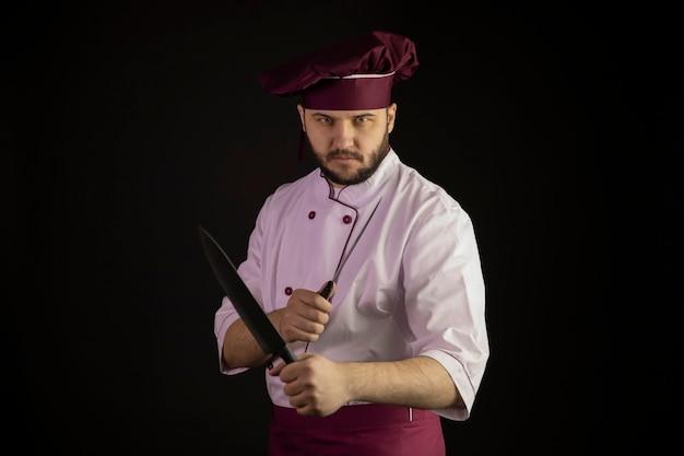 Bel giovane chef maschio barbuto in uniforme tiene coltelli affilati incrociati