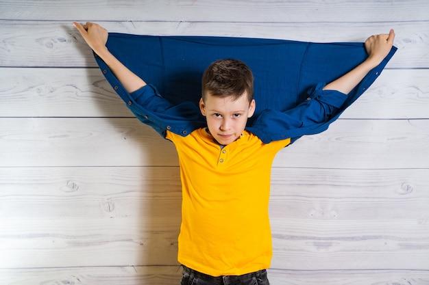 Bel giovane ragazzo che propone alla macchina fotografica con le mani e la giacca sulla schiena