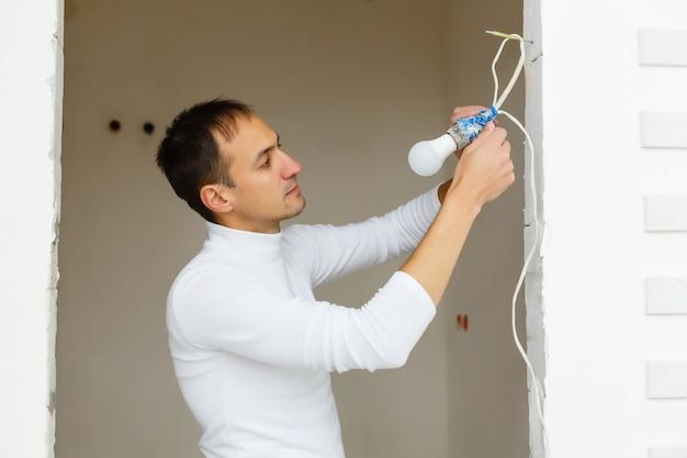 Il giovane costruttore bello in un casco giallo della costruzione sta torcendo la lampadina dentro. l'uomo sta cercando.