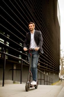 Bel giovane uomo d'affari in un abbigliamento casual in sella a uno scooter elettrico da un edificio per uffici in occasione di una riunione di lavoro