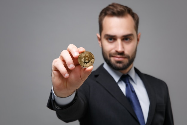 Bel giovane uomo d'affari in classico abito nero camicia cravatta in posa isolato sul muro grigio. realizzazione carriera ricchezza concetto aziendale. tenendo bitcoin, valuta futura.