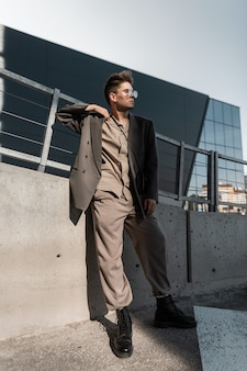 Bel giovane modello di uomo d'affari con occhiali da sole eleganti in abito grigio alla moda si trova in città alla luce del sole. stile urbano elegante maschile, moda e successo