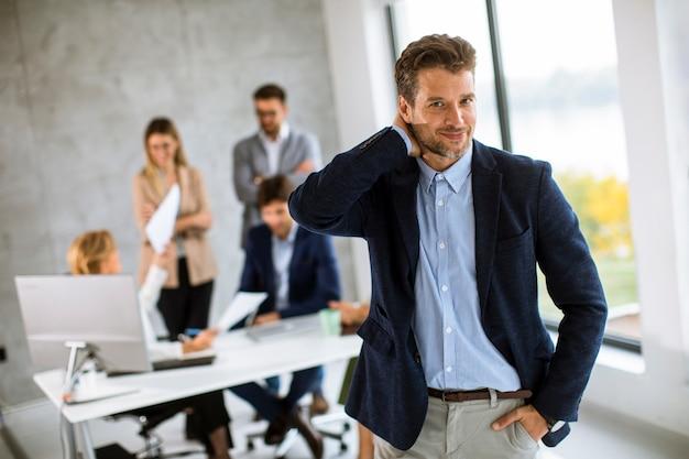 Bel giovane uomo d'affari in piedi fiducioso in ufficio davanti alla sua squadra
