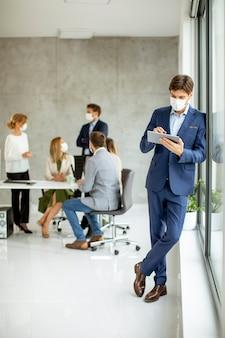 Bel giovane uomo d affari che indossa la maschera protettiva facciale mentre si tiene la tavoletta digitale nello spazio ufficio