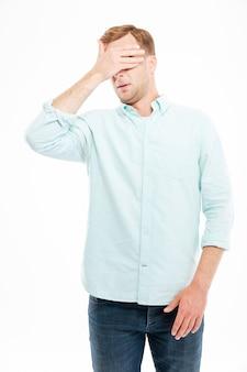 Un bel giovane uomo d'affari si coprì gli occhi a mano sul muro bianco