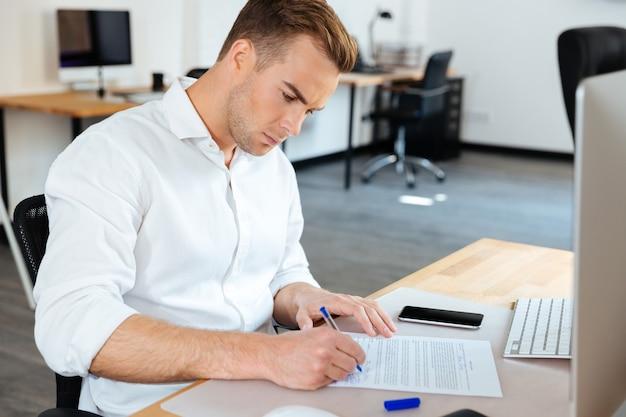 Bel giovane imprenditore seduto e firmare documenti in ufficio