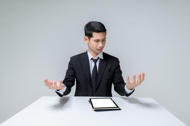 Bel giovane imprenditore seduto a un tavolo e alzando entrambe le mani e guardando le sue mani. uomo bello con la compressa e la tavola isolate su bianco