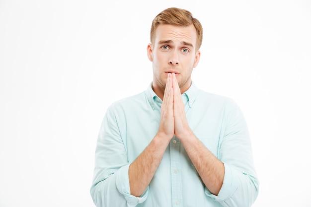 Bel giovane uomo d'affari in piedi e pregando