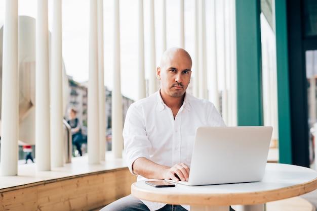Bel giovane uomo d'affari in una camicia bianca, seduti in un caffè e lavorare con un computer portatile